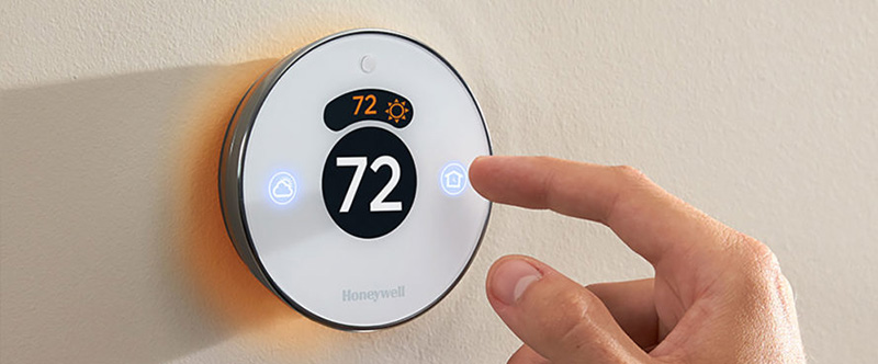 A hand adjusting the Honeywell thermostat
